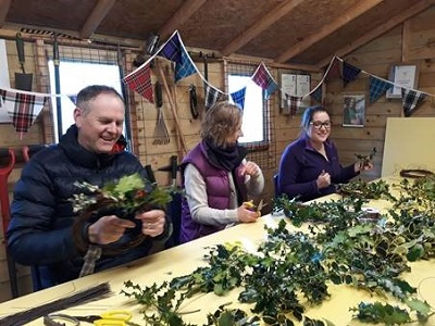 Volunteers making holly balls and wreaths